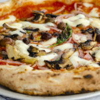 Close up of traditional Capriciosa in italian restaurant. Front view. Italian pizza concept